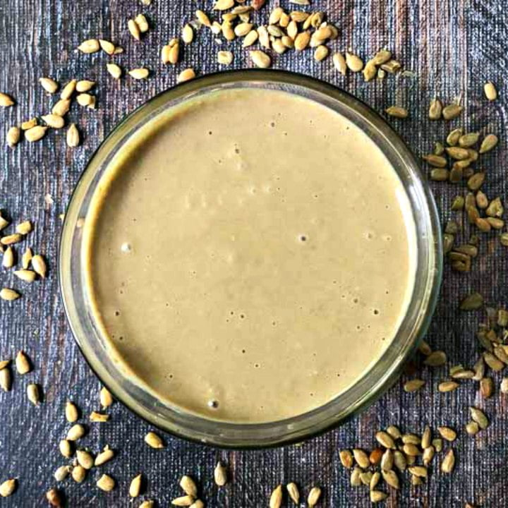 glass bowl with keto homemade sunflower seed butter and sunflower kernels scattered around