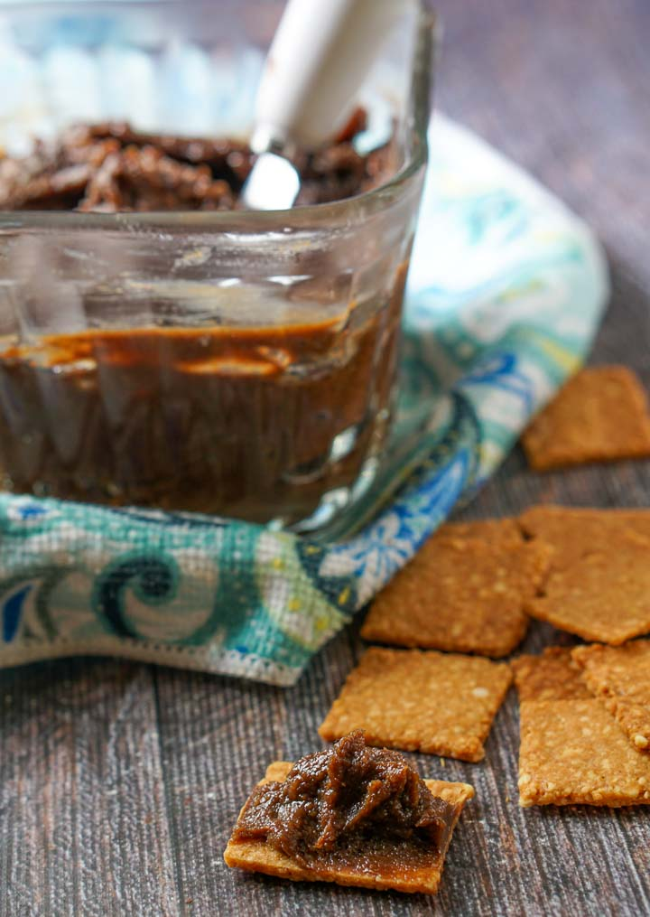 a homemade cracker with a bit of chocolate sunflower seed butter and glass dish in the background