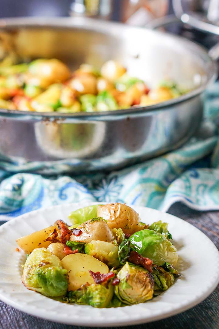 white plate with Brussels sprouts & potatoes side dish and pan in background