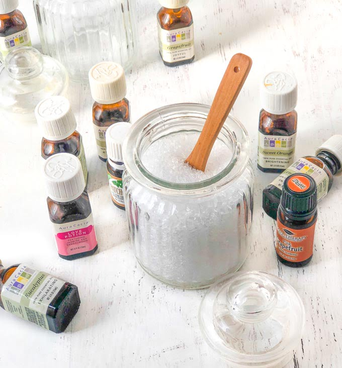 essential oil bottles and a jar of bath salts with wooden spoon
