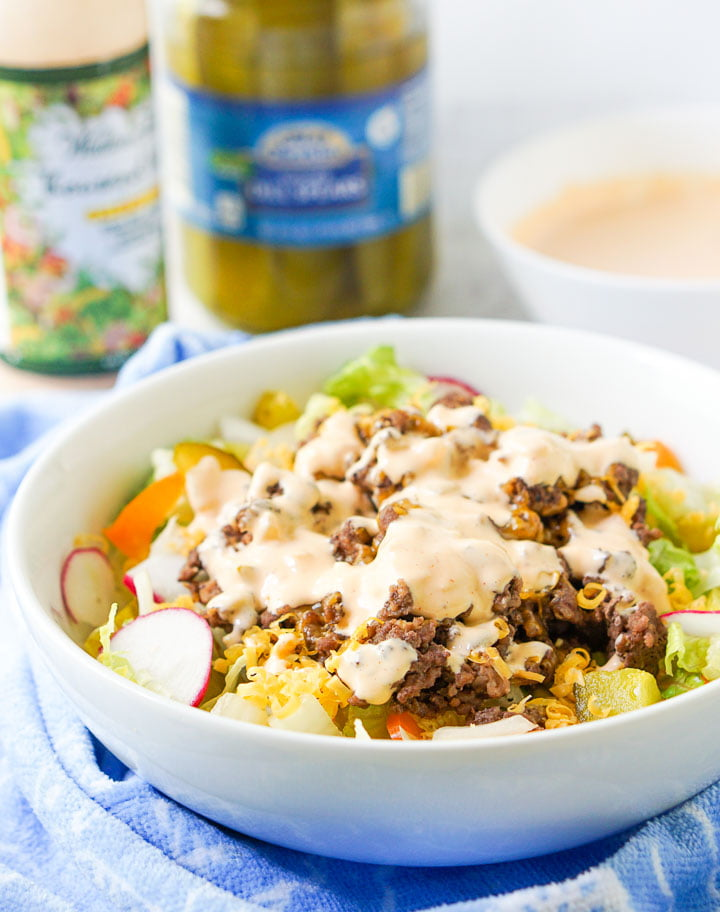 white bowl with Big Mac salad and a jar of pickles and special sauce dressing in the background