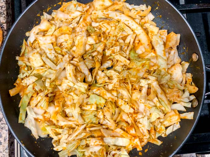 skillet with raw cabbage noodles mixed with red curry sauce