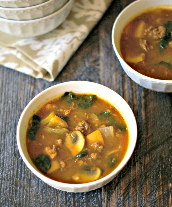two white bowls with paleo pumpkin soup with sausage and kale