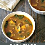 white bowl with paleo pumpkin soup with sausage and kale and text overlay