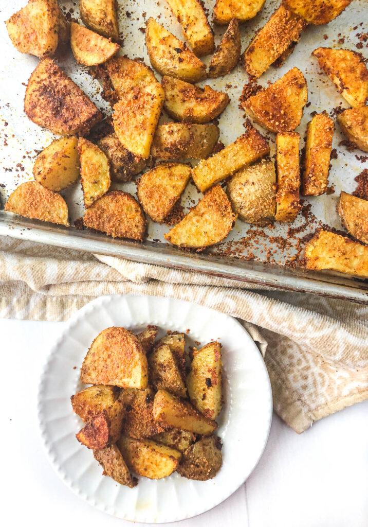 seasoned roasted potatoes on a baking sheet and white plate