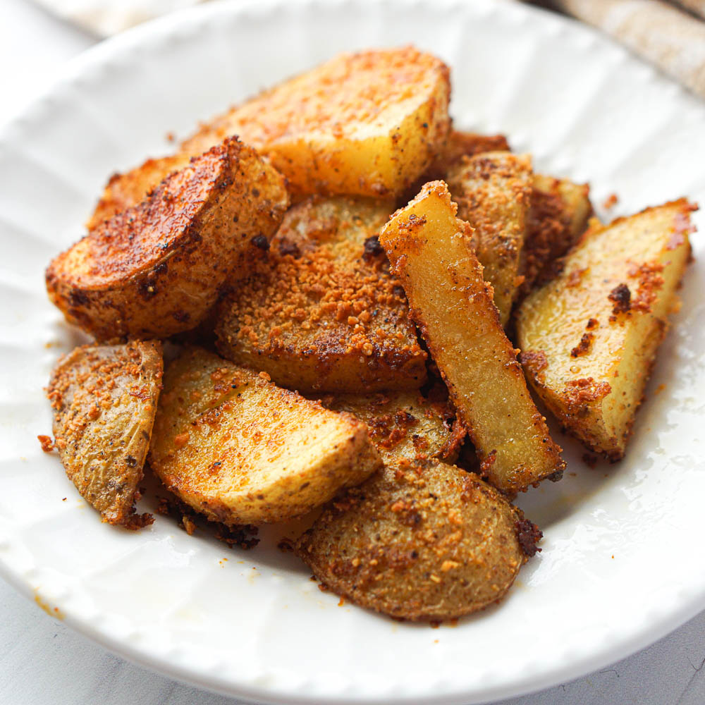 closeup of spicy roasted potatoes on a white plate
