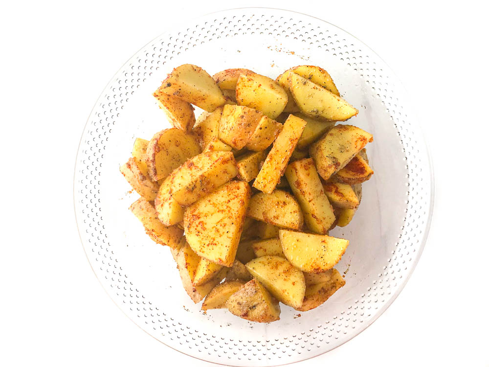 glass bowl with raw potatoes covered in spices