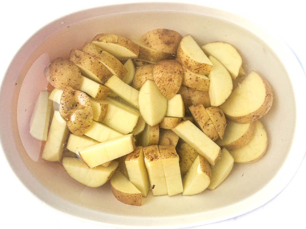 baking dish with raw potato pieces covered in water