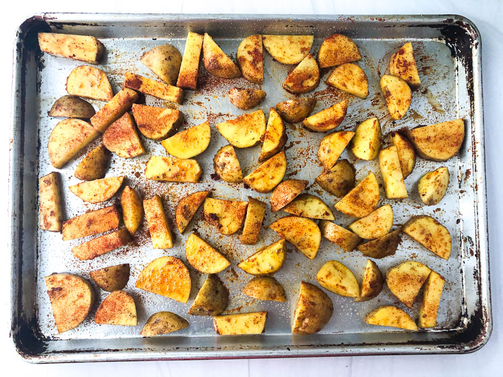 baking sheet with spicy potato wedges ready for the oven