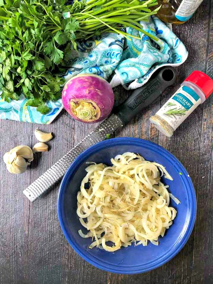 blue bowl of turnip noodles, a microplane, garlic cloves, parsley and a bottle of rosemary