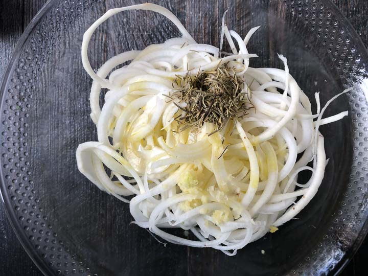 raw turnip noodles in a glass bowl with dried rosemary, garlic and olive oil on top