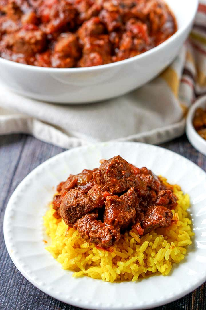 white plate with yellow rice and easy beef curry and bowl in background