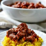 white bowl and plate with beef curry with text