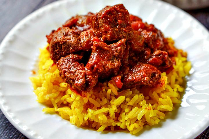 white plate with yellow rice and beef curry