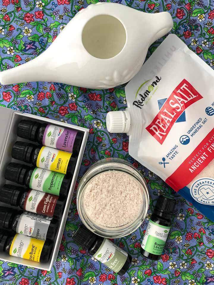 aerial view of Real salt, Plant Therapy essential oil kit, a white neti pot and a jar of salts