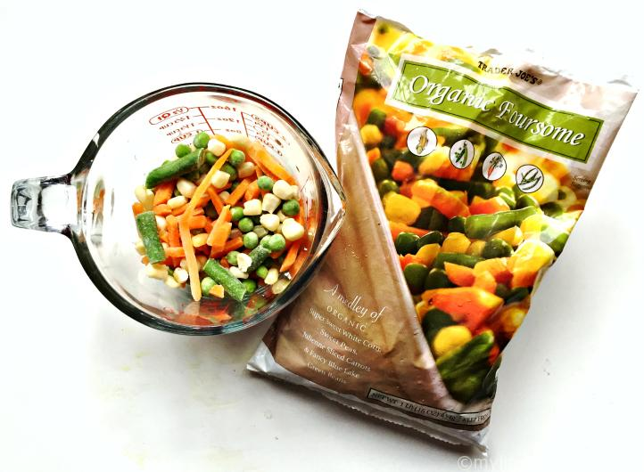 measuring cup with frozen mixed vegetables and the bag from Trader Joes for pot pie soup