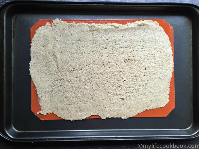 Cracker dough spread out on cookie sheet