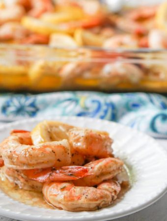 white plate with a few keto cajun shrimps with a baking dish in background