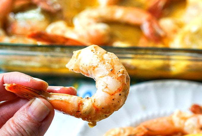 hand holding 1 cooked cajun shrimp