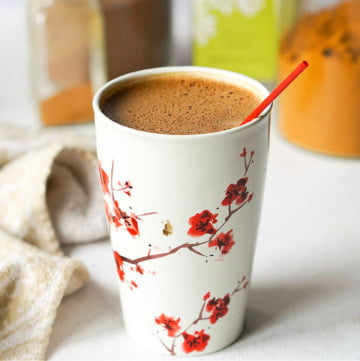 white mug with red flowers with mocha maca matcha drink