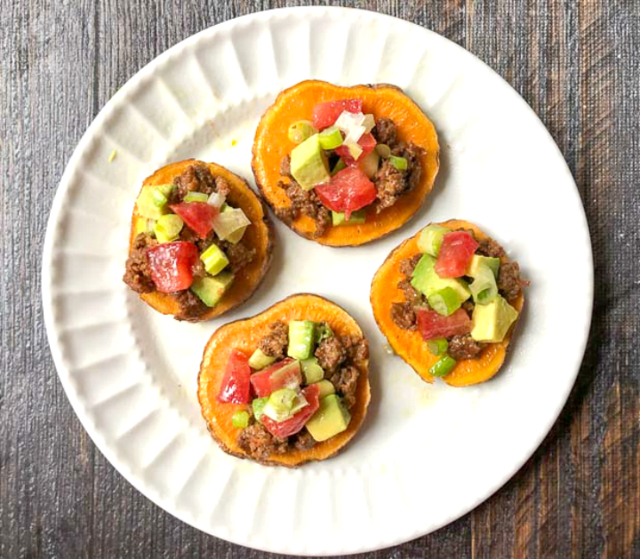 white plate with 4 sweet potato slices topped with nacho toppings