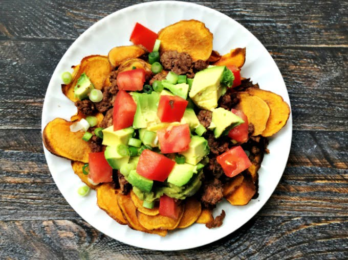 Two ways to serve Paleo Nachos. One in a pile of sweet potato chips or as individual chips topped with nacho ingredients for easy handling. Both delicious!