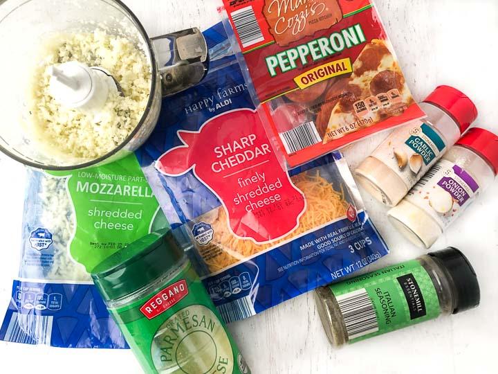 recipe ingredients: shredded mozzarella and cheddar, pepperoni, cauliflower rice, parmesan, onion powder, garlic powder and Italian seasonings
