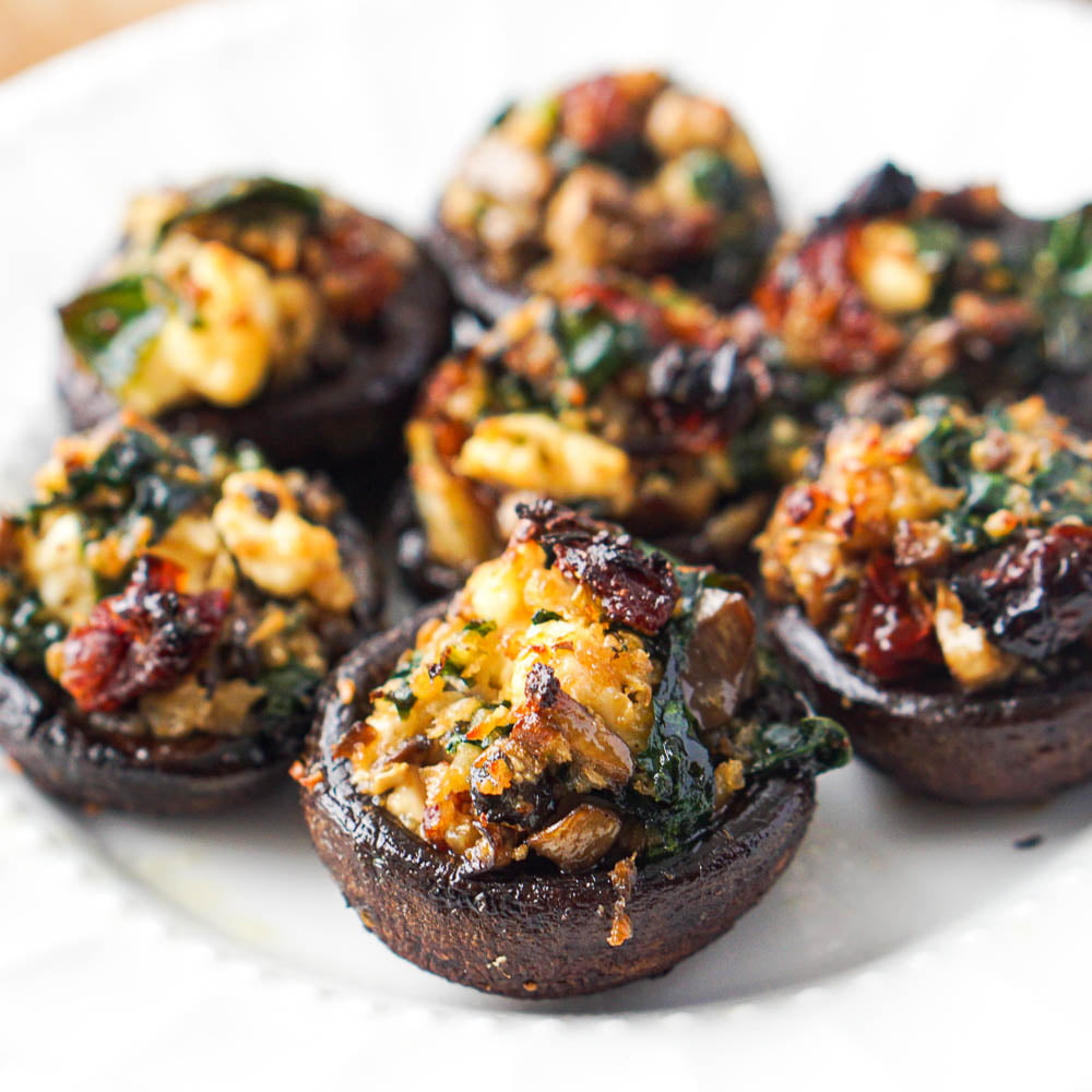 closeup of vegetable stuffed mushrooms with feta cheese, sun-dried tomatoes and spinach
