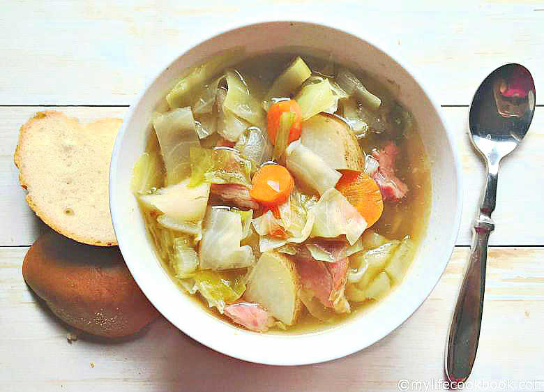 a bowl of ham and cabbage soup with a spoon and some bread slices