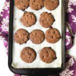 cookie sheet with keto chocolate chip cookies on purple towel with text overlay
