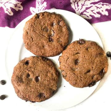 white plate with 3 keto 5 ingredient cookies and scattered chocolate chips