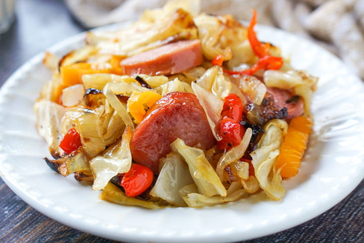 white plate with kielbasa & cabbage casserole