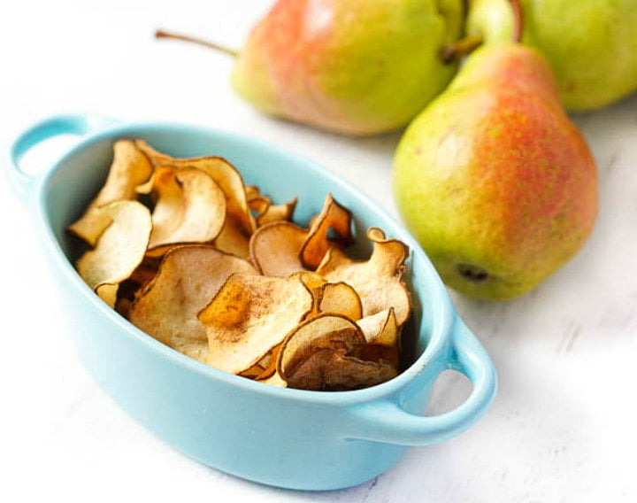 blue dish with pear chips and fresh pears in the background