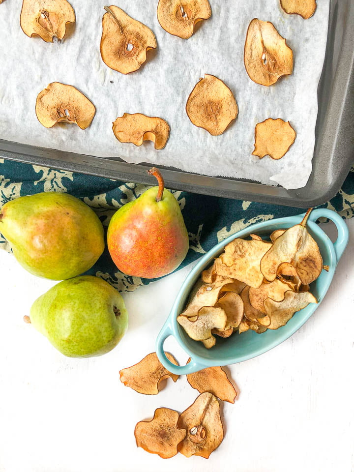 cookie sheet and blue bowl with pear chips and few scatter fresh pears