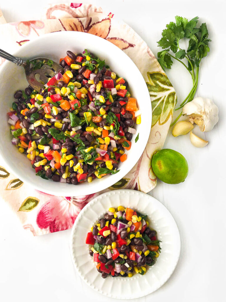 aerial view of white bowl and plate with black bean and corn salad with a lime, garlic and cilantro bunch