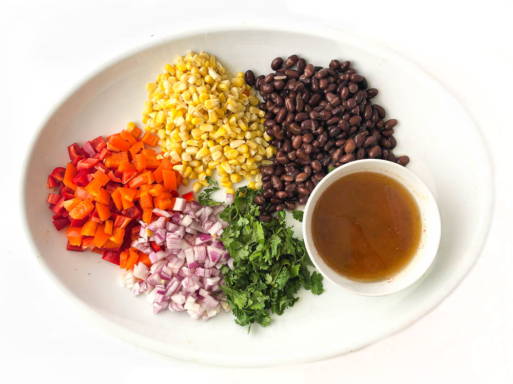 ingredients use for picnic salad - black beans, corn, peppers, onions, cilantro and bowl of dressing