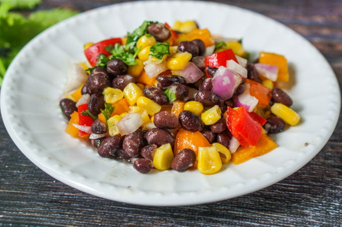 Mexican Bean Salad is perfect for summer picnics and parties that you can make the night before. The festive colors & delicious taste are sure to be a hit.