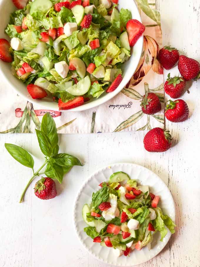 white bowl and plate full of strawberry caprese salad and fresh basil and strawberries on the side