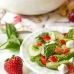 bowl and plate with strawberry caprese salad and text overlay