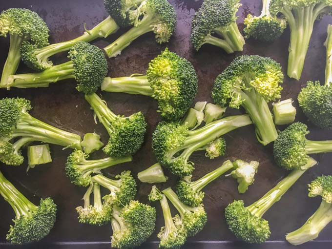 raw broccoli florets on cookie sheet