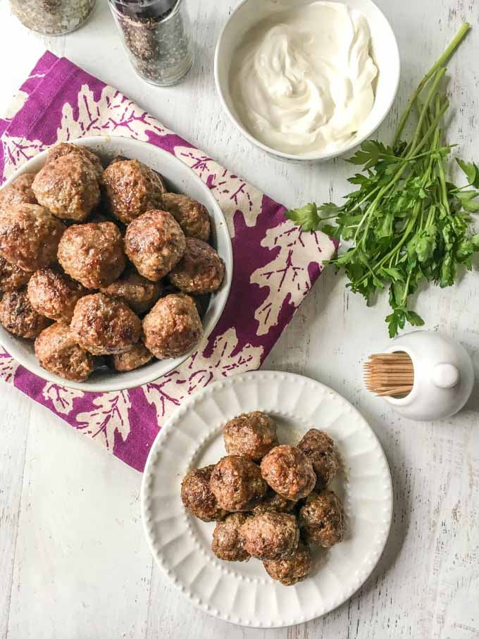 Long photo of a white plate of meatballs with a  bowl of meatballs and yogurt and parsley.
