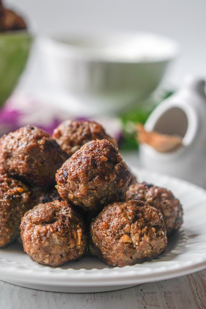 Long photo of a closeup of meatballs on a white plate.