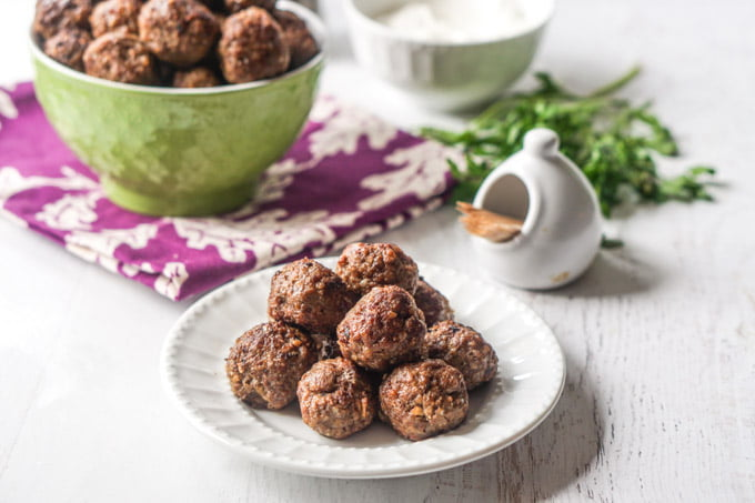 Photo of a white plate of middle eastern meatballs with a green bowl in background.
