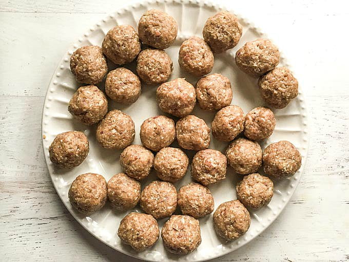 White plate of raw meatballs.