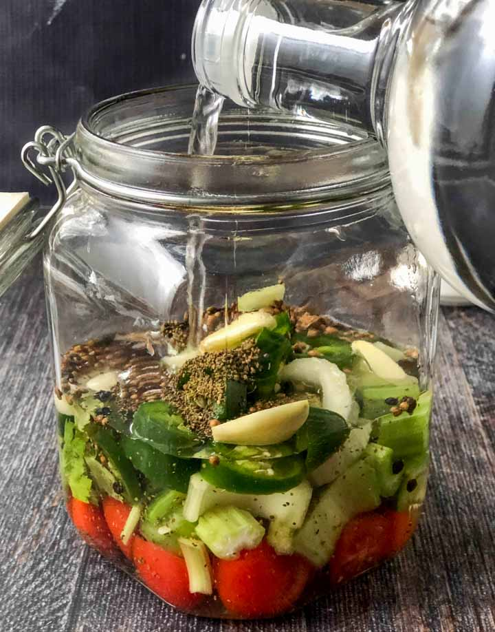 pouring vodka over the vegetables in a large glass jar