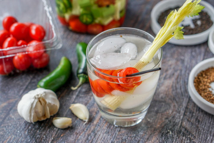 glass with ice, tomato on a stir and celery stalk with garlic, jalapenos and tomatoes in the background