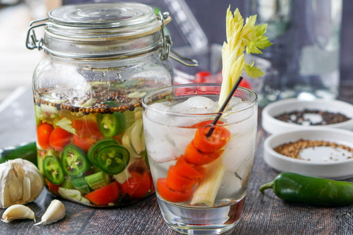 jar with Bloody Mary infused vodka in a jar and a drink with tomatoes and celery stalk