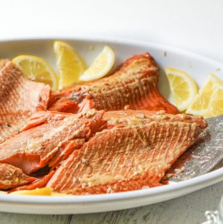 white platter with smoked salmon and lemons