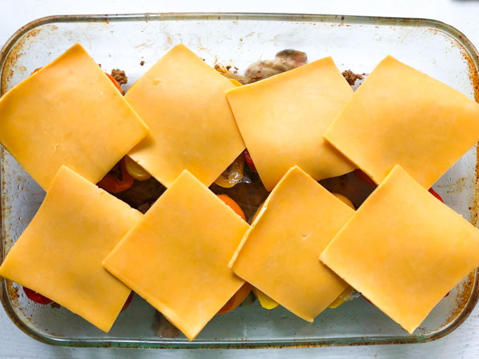 baking dish with taco peppers with a slice of cheese on top before cooking
