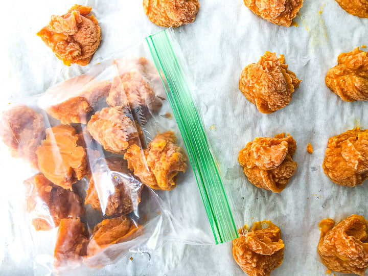 baggie and cookie sheet with frozen mounds of pumpkin puree